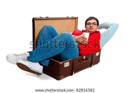 A young man with glasses and a red waistcoat poses lying down in a large antique trunk in the studio on a white background