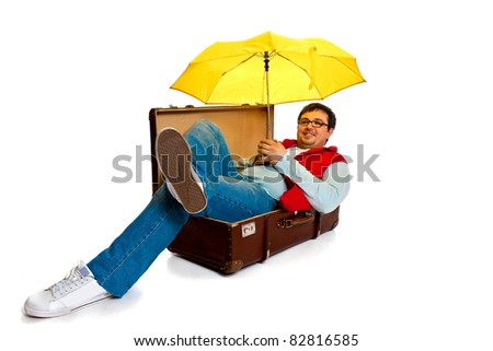 A young man with glasses and a red waistcoat poses lying down in a large antique trunk in the studio on a white background - stock photo