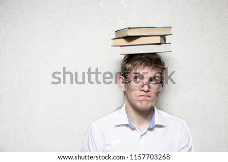 A young man with glasses and a white shirt with books on his head
