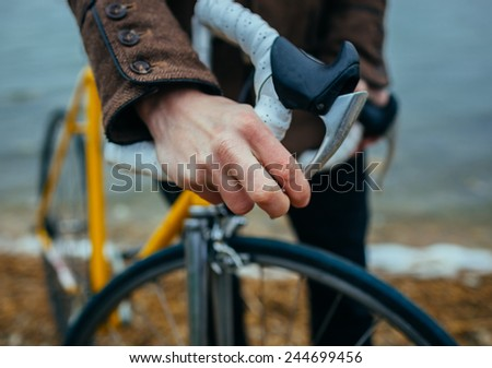 a young man with hands on the steering wheel of bicycle near the lake