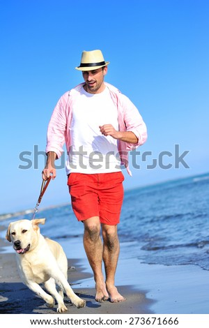 A young man with his dog walking on the beach - stock photo