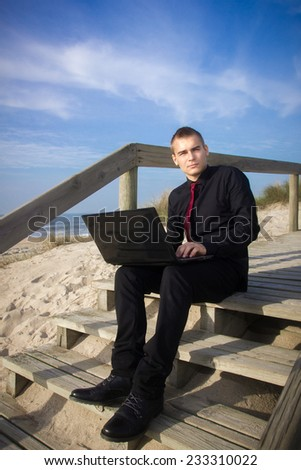A young man with laptop sitting on the beach