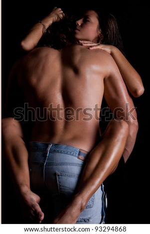 A young man with long hair and a muscular back passionately engaged in sex with a beautiful girl at the wall - stock photo