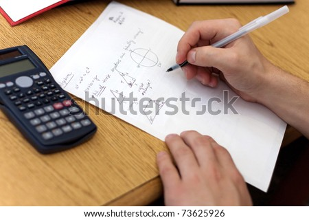A young man working out mathematical equations on paper. - stock photo
