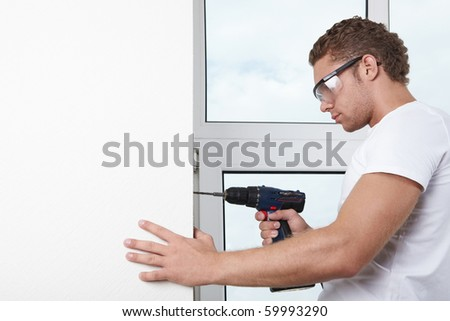 A young man working with a drill - stock photo