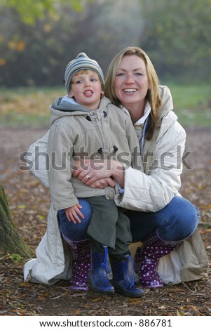 A young mother and her son wrapped up well against the cold and having a cuddle.
