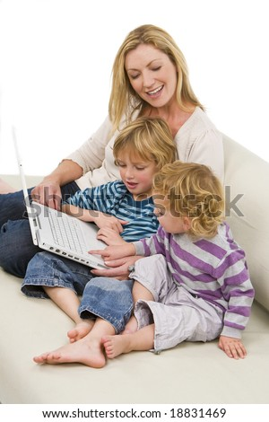 A young mother and her two children using a laptop at home on a settee