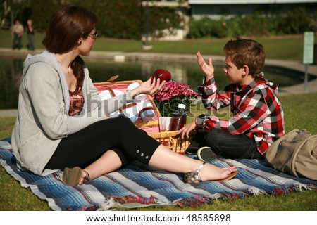 a young mother and son enjoy a picnic together in a park - stock photo