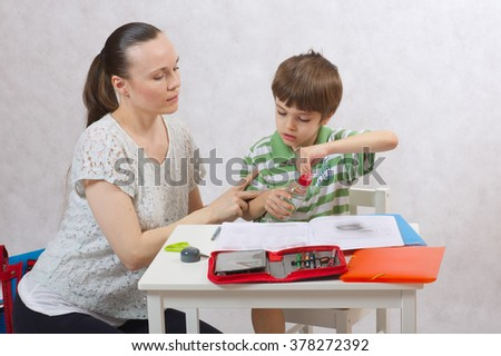 A young mother ask her six years old child to drink some water while he is doing his homework. White background