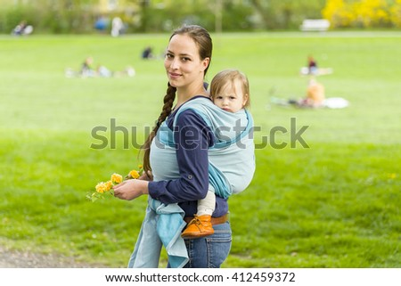 A young mother carrying her little baby in a sling on her back and walked in beautiful sunny weather by a park. The two laugh and have fun
