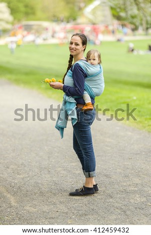A young mother carrying her little baby in a sling on her back and walked in beautiful sunny weather by a park. The two laugh and have fun - stock photo