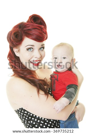 A young mother dressed in Rockabilly style holding her 8 month old teething son.  Shot on white background.