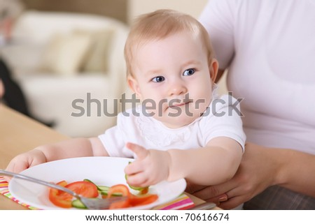 a young mother feeding her infant baby at home - stock photo