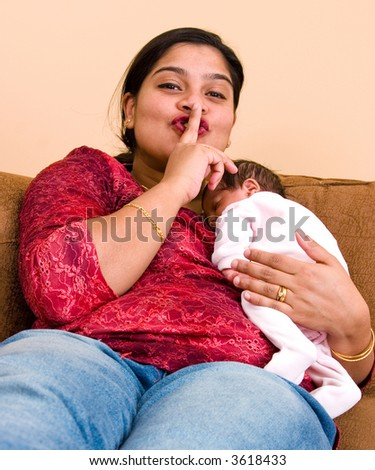 A young mother gestures for some quiet time as her baby sleeps - stock photo