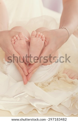 A young mother holding her baby foot. Hands folded in the shape of a heart. Close-up portrait. The concept of happiness in the birth of children. - stock photo