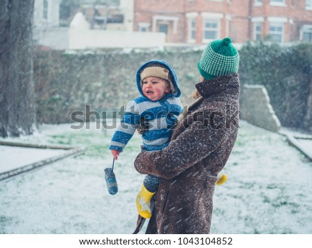 A young mother is carrying her toddler in the snow