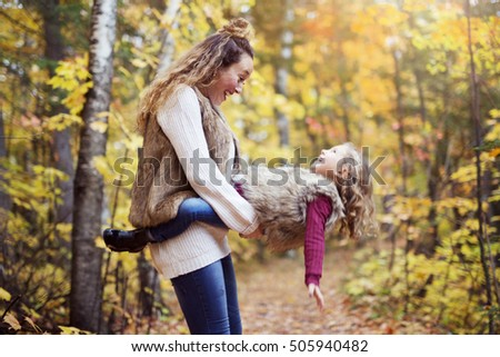 A Young mother playing with her daughter in autumn park