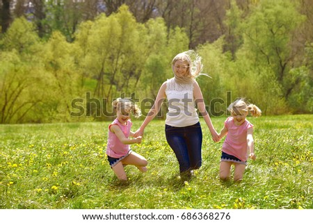 A young mother takes her twin daughters for a walk  in a flower field. They have fun running and jumping  over flowers.