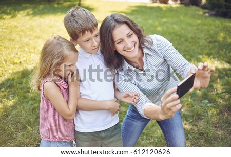 A young mother with children walks in the park and does selfie with them. Mom's daughter and son on a walk