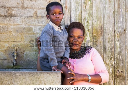 A young mother with her little boy outside their home. - stock photo