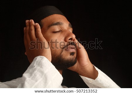 A young Muslim religious man prays in darkness