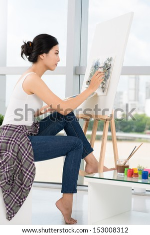 A young painter busy with drawing at his workplace
