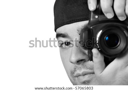 A young photographer taking a photo with his digital single lens reflex camera with selective color. - stock photo