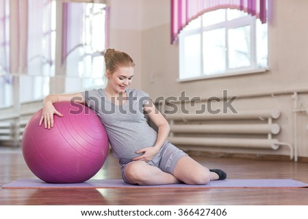 A young pregnant woman doing gymnastic exercises with fitball, dumbbells on the mat at the gym. - stock photo