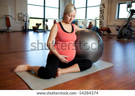 A young pregnant woman doing relaxation exercise using a fitness ball while sitting on a mat and holding her tummy - stock photo