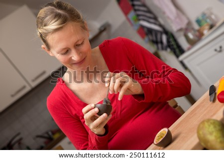 a young pregnant woman eating a fresh passion fruit - stock photo