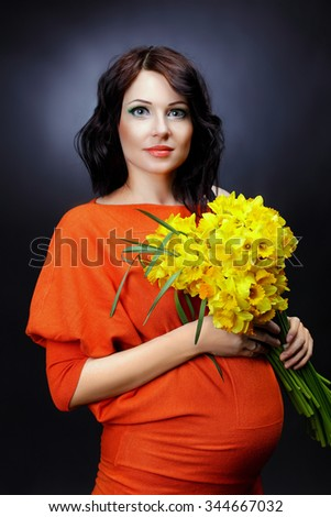 A young pregnant woman holding a bouquet of yellow flowers in hand, a healthy pregnancy. Happy pregnant woman smiling. Beautiful pregnant woman holding her tummy.