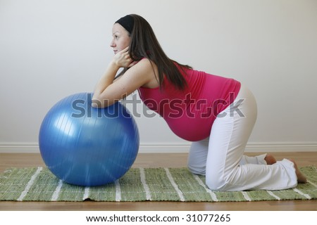 A young pregnant woman in a pink shirt doing an abdominal muscle exercise using a blue fitness ball. - stock photo