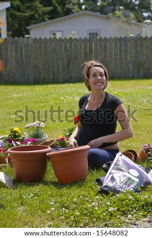 a young pregnant woman planting flowers in pots.