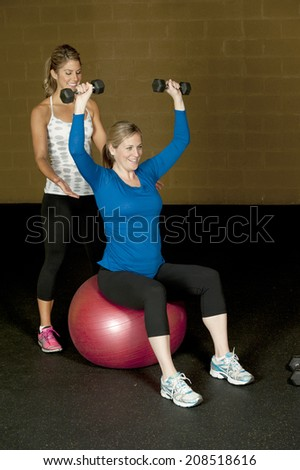 A young pregnant woman working out with an atletic female trainer at the gym.