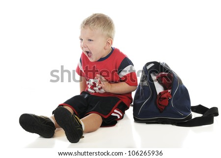 A young preschool athlete, sitting by his gym bag yelling at his team mates.  On a white background. - stock photo