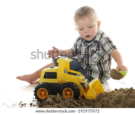 A young preschooler playing in sand with a toy scoop and bulldozer.  On a white background.