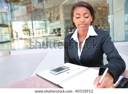 A young pretty african american woman studying outside library at school - stock photo