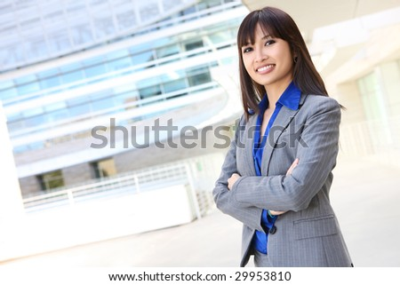 A young, pretty asian business woman at office building - stock photo