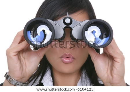 A young pretty asian business woman looking through binoculars - stock photo