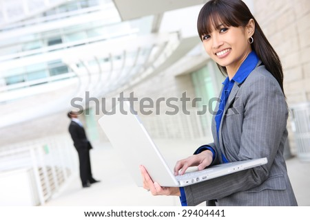 A young pretty asian business woman on laptop computer at work - stock photo