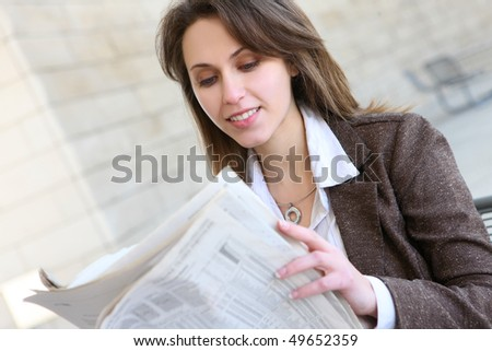 A young pretty business woman reading the newspaper at office building - stock photo