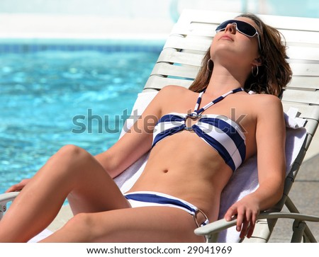 A young pretty Girl sunbathing by the pool - stock photo