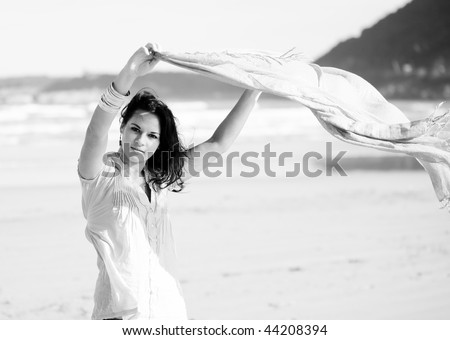 a young pretty girl with a scarf in a beach in a sunny beach - stock photo