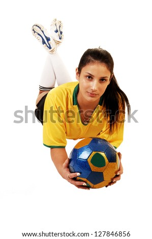 A young pretty soccer girl lying on the floor in her uniform, yellow top and black shorts, with a soccer ball in her hand for white background. - stock photo
