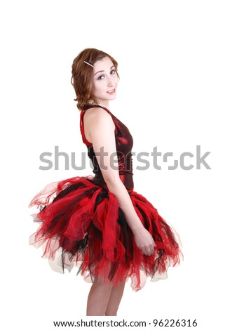 A young pretty teenager in a red and black ballet outfit with a big twill skirt standing in profile for white background in the studio.