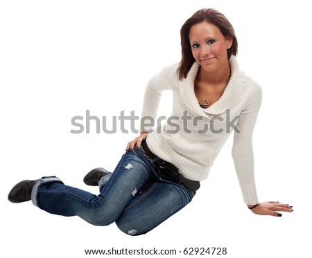 A young, pretty woman in white sweater and jeans smiles while sitting on floor. Studio shot on white. - stock photo