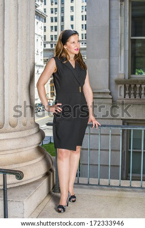A young pretty woman is standing outside an office building, a hand resting on her hips, a hand touching railings, relaxing and thinking. / Thinking Outside - stock photo