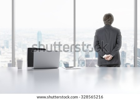 A young professional is looking out the window in the modern panoramic office in Manhattan, New York City. A laptop, notepad and a coffee cup are on the white table. - stock photo