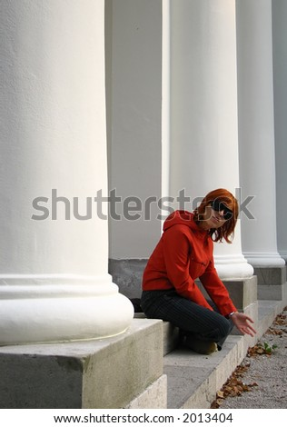 A young redhead sitting in a colonnade and playing with the sand.