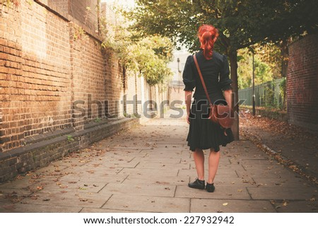 A young redhead woman is walking in a cobbled alley in the autumn on a sunny day